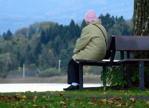 alte Frau wartet auf einer Bank